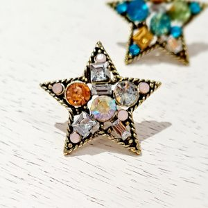 A star brooch pin with a twisted gold wire frame and colourful clear crystals in pinks