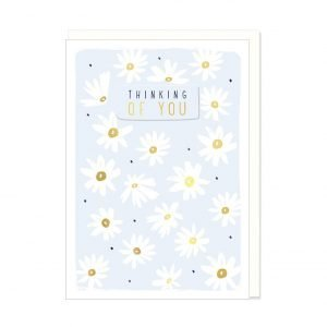 A pale blue card with lots of little white daisies and the words Thinking of You