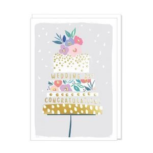 A wedding card with a contemporary illustration of a layered wedding cake with gold foil details and flowers in pinks and purples and wedding congratulations in gold writing