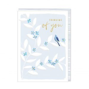 A pale blue card with branches of white leaves and blue flowers with a single blue bird perched on one of the branches and Thinking of you printed in gold