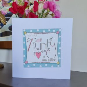 A white card with a square of teal polka dot paper stitched on to it with a further white square with the a hand illustration of the word Aunty decorated with little hand drawn hearts and stars. To a special Aunty Happy Birthday