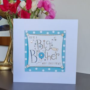 A card to congratulate a little boy on becoming a big brother. A white card with a square of teal polka dot paper stitched on to it with a further white square with a hand illustration of the words Big Brother decorated with little balloons and stars. You're a big brother what lovely news.
