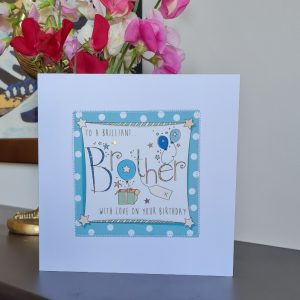 A white card with a square of teal polka dot paper stitched on to it with a further white square with a hand illustration of the word Brother decorated with little balloons, presents and silver stars. To a brilliant Brother with love on your birthday.