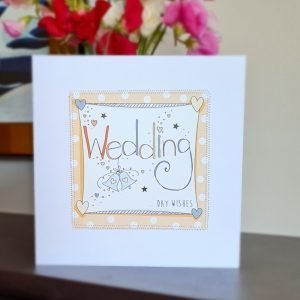 A white card with a square of orange polka dot paper stitched on to it with a further white square with the A hand illustration of the word wedding decorated with little hearts and stars and wedding bells
