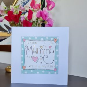 A Mummy birthday card. A white card with a square of pink polka dot paper stitched on to it with a further white square with a hand illustration of the word Mummy decorated with little hearts and stars. To a special Mummy with love on your birthday.