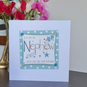 A white card with a square of teal polka dot paper stitched on to it with a further white square with the a hand illustration of the word Nephew decorated with little balloons and silver stars. To a special Nephew with love on your birthday.