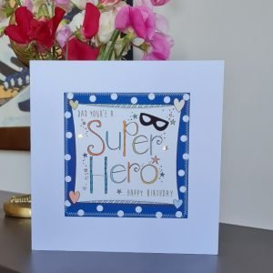 A birthday card for a super hero Dad. A white card with a square of navy blue polka dot paper stitched on to it with a further white square with a hand illustration of the words Super Hero decorated with a little super hero mask and hand drawn stars. Dad you're a super hero Happy Birthday