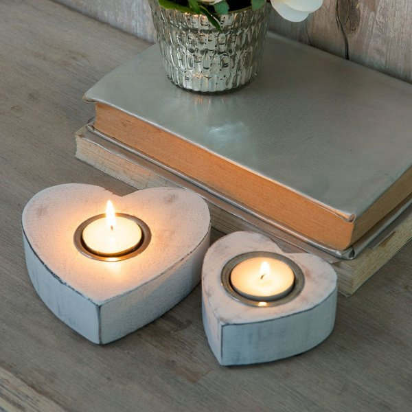 A pair of white wooden heart tealights that have been painted with a chabby chic white effect.