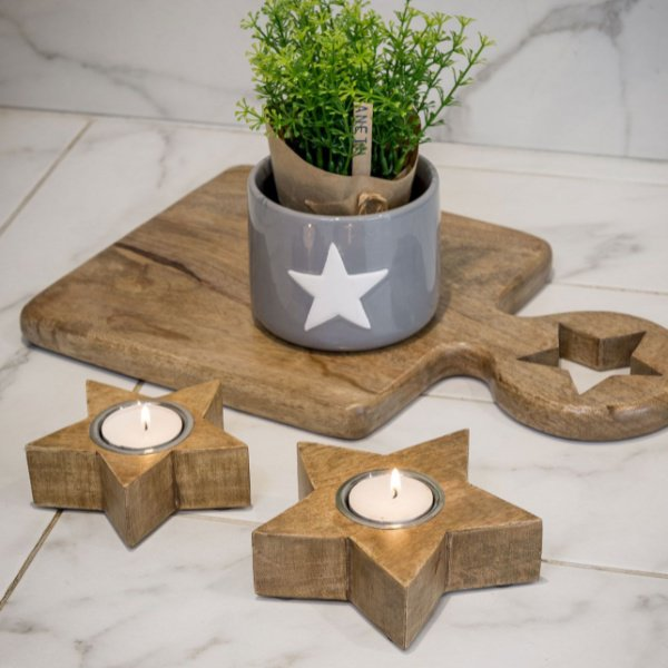 A pair of natural wooden star shaped tealight holders.