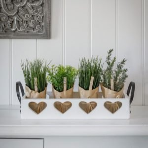 A white ornamental trug with cut out hearts and handles at each side. Finished with a white shabby chic paint effect.