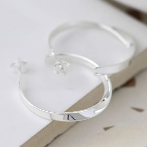 A pair of sterling silver flat hoop sleeper earrings which have a twist effect.