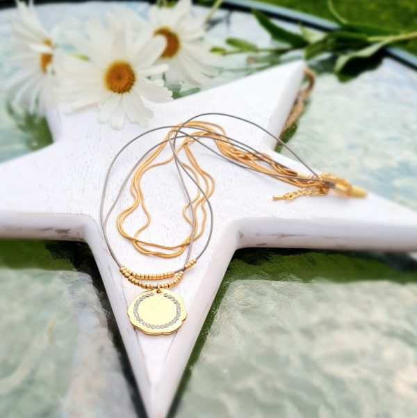 A delicate designed short necklace in matt gold. Three strands of slinky snake chain, teamed with a duo of fine faux leather cords hosting dainty seed beads, all to showcase a gorgeous circle of mini sparkle on a flat metallic old gold pendant.