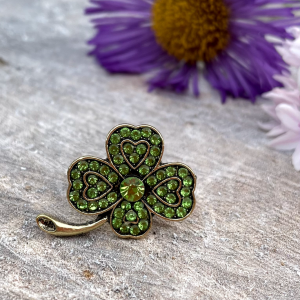 A sparkly green brooch in the shape of a four leaf clover that is covered in green diamanté jewels.
