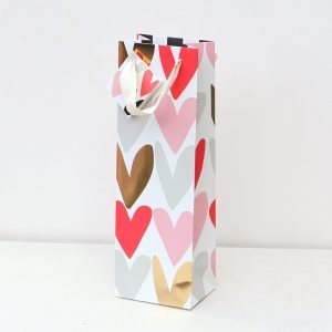 A tall bottle bag with white ribbon handles and a gift tag and a mix of hearts in pink, red, grey and metallic gold