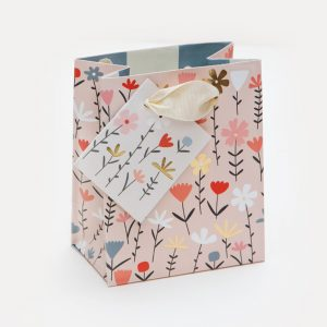 A small pink gift bag with a flower pattern in reds, pinks, white and orange.