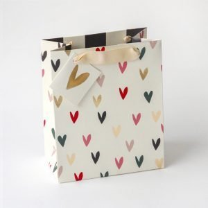 A medium gift bag with lots of little hearts on a cream bag
