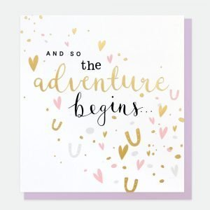 A wedding card with gold foil horeshoes and hearts and the words and so the adventure begins