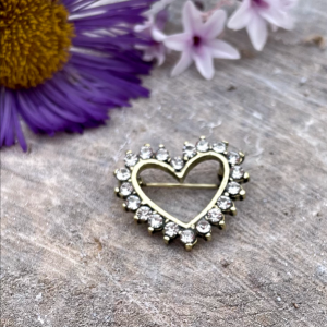 A sparkly heart shaped brooch that is covered in little diamanté jewels