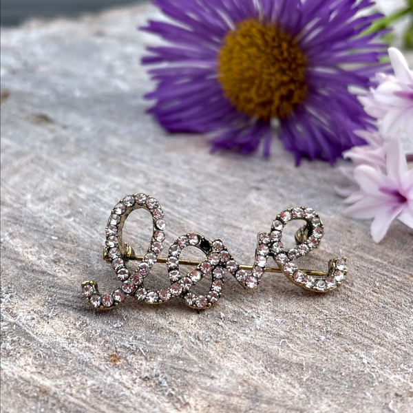 A sparkly brooch in the shape of the word love which is covered in diamanté jewels.