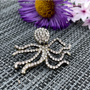 A glittery brooch in the shape of an octopus covered in little diamanté jewels.