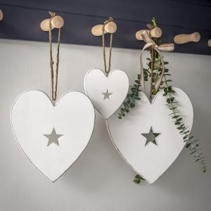 A white distressed effect wooden hanging heart with a little cut out star in the middle. A choice of three sizes