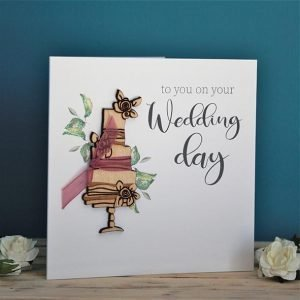 A square white card with a wooden wedding cake with little ribbons and the words To you on your wedding day printed on it.