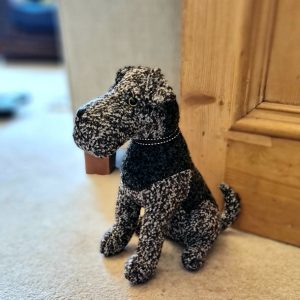 A fabric airedale terrier dog door stop. Made from durable brown speckled boucle fabric with dark patches