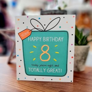 An 8th birthday card. A big bright green present on a spotty backgrount with Happy Birthday 8 today you're eight and totally great written in the present