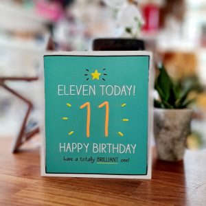 An 11th birthday card. A green card with a yellow star a big neon orange 11 and 11 today Happy birthday have a totally brilliant one