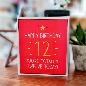 A neon bright red 12th birthda card. A big orange 12 and an orange star with white writing. Happy Birthday 12 You're totally twelve today!