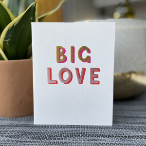 A white card with the words Big Love Printed in colourful embossed lettering