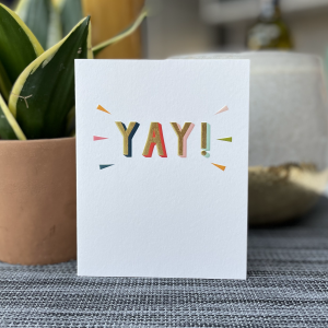 A white card with the word YAY Printed in colourful embossed lettering