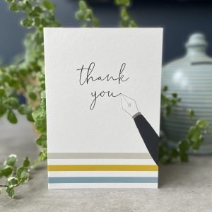 A white card with three colourful lines at the bottom of it and an image of a fancy ink pen which appears to be writing the words Thank You on it