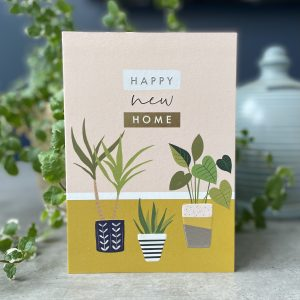 A card with images of plants and lovely planters. The words Happy New Home are printed and embossed at the top of the card.
