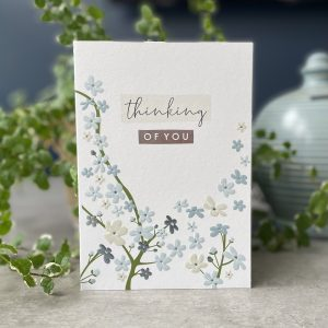 A beautiful card with a spring blossom tree design in muted colours. The words Thinking of You are printed above the blossom.