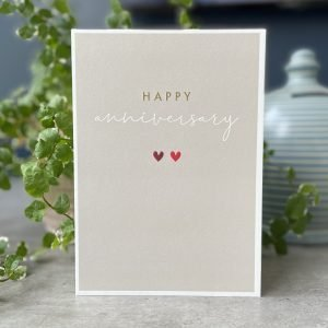 A beige coloured card with two little hearts that have been printed and embossed in the centre of the card. The word Happy is printed in gold lettering and the word anniversary is printed in white.