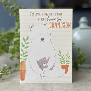 A cute card with an image of a large bear holding a smaller bear. The words Congratulations of the birth of your beautiful Grandson printed on it.