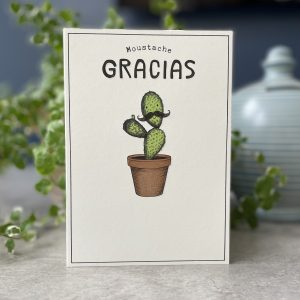 A cream coloured card with an image of a cactus in a pot with a face on the top section . The face has a curly moustache on it. The words Moustache Gracias are printed above the cactus image.