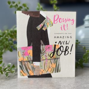 A card with an image of a woman in a suit carrying a colourful brief case. The words Bossing it Congrats on the amazing new job printed on it.