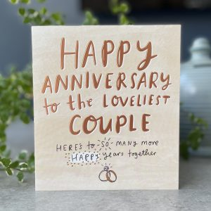A cream coloured square card with the words Happy Anniversary to the loveliest couple printed in copper lettering . Here's to so many more happy years together are printed on the bottom of the card in black lettering. There is an image of 2 intertwined rings at the very bottom of the card.
