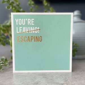 A lovely mint green coloured square card with the words You're leaving printed and embossed in white but with the word leaving crossed out and the word Escaping printed and embossed below it in gold.