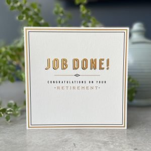 A white card with the words Job Done printed and embossed in gold. The words Congratulations on your retirement are printed below in black and gold writing.