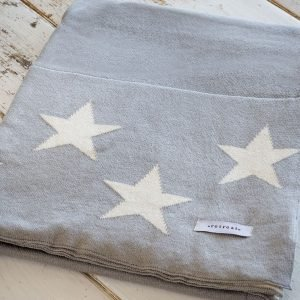 A supersoft reversible throw that is dove grey and cream with little stars on it