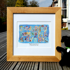 A blue alphabet personalised framed print which is from an original watercolour painting. The print can be personalised with a name and date of birth or a christening date.