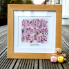 A personalised pink alphabet print which has been framed in an oak wooden frame.
