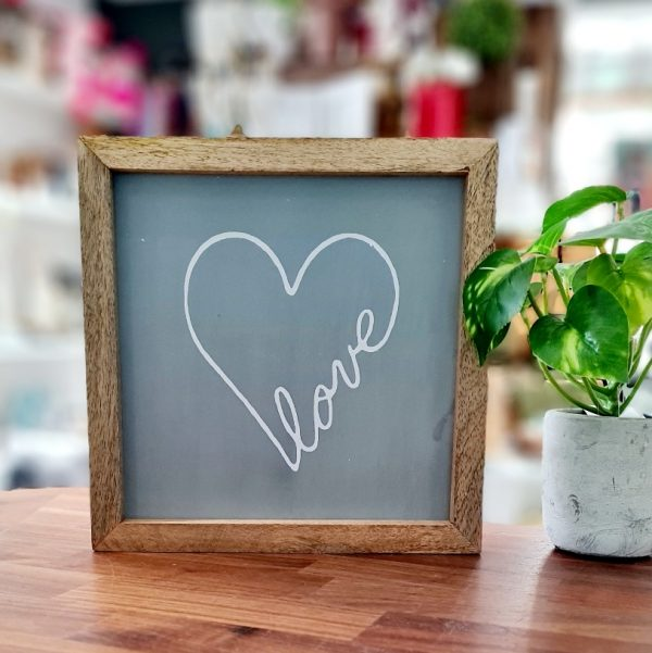 A grey coloured wooden panel printed in white with the word love included as part of a love heart. The grey panel is framed in a natural wood frame