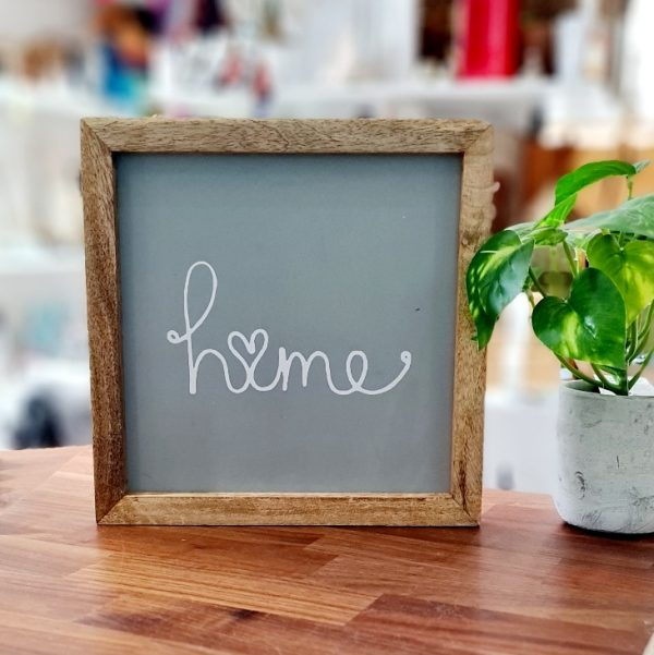 A grey coloured wooden panel printed in white with the word home with a heart as the o The grey panel is framed in a natural wood frame