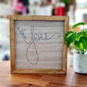 Love Arrow Wooden Panel. A panel of ash coloured wood printed with the words love you in a grey hand writing style. The panel is framed in a natural wood frame