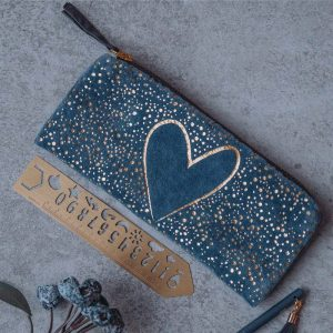 A blue pouch with a gold spotty effect and a large gold heart printed on the front of the pouch. With a gold zip fastening and velvet tag.