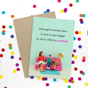 A rude card from Jeffrey and Janice with a photo of 2 barbie dolls posed on a sofa with a child doll and a baby doll. Although frowned upon it isn't actually illegal to call a child an arsehole